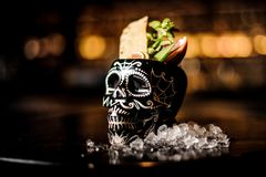 Cocktail in the black skull cup in mexican style with tropical fruits. Tropical cocktail in the black skull cup in mexican style with pineapple, lemon stock photo