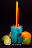 Cocktail bleu avec des cerises, mangue, orange, chaux, pamplemousse sur un fond d'isolement photographie stock libre de droits
