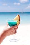 Cocktail bleu du Curaçao dans la main femelle photographie stock
