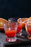 Cocktail with Blood oranges. Close up of Shorts of alcohol cocktail with Sliced Sicilian Blood oranges and fresh red orange juice, served on black wooden table royalty free stock photo