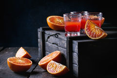 Cocktail with Blood oranges. Shorts of alcohol cocktail with Sliced Sicilian Blood oranges and fresh red orange juice, served on black wooden chest over old stock image