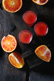 Cocktail with Blood oranges. Shorts of alcohol cocktail with Sliced Sicilian Blood oranges and fresh red orange juice, served on black wooden chest over old royalty free stock photos