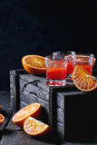 Cocktail with Blood oranges. Shorts of alcohol cocktail with Sliced Sicilian Blood oranges and fresh red orange juice, served on black wooden chest over old stock photos