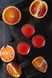 Cocktail with Blood oranges. Shorts of alcohol cocktail with Sliced Sicilian Blood oranges and fresh red orange juice, served on black wooden chest over old stock photo