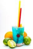 Cocktail blu con le ciliege, mango, arancia, calce, pompelmo su un fondo isolato Immagini Stock Libere da Diritti