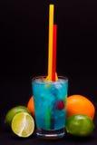 Cocktail blu con le ciliege, mango, arancia, calce, pompelmo su un fondo isolato Fotografia Stock Libera da Diritti