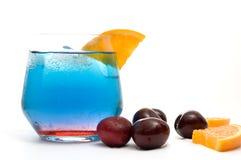Cocktail blu operato isolato con le fette e le ciliege arancio Immagini Stock