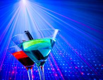 Cocktail with blue light disco background with space for text Royalty Free Stock Photo