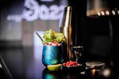Cocktail in the blue steel cup with mint and red berries. On the bar counter stock photography