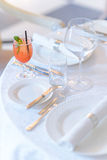 Cocktail with a bunch of mint served on the table. Ice cocktail at the served table among the empty plates and glasses royalty free stock photo