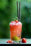 Cocktail capirosca. Red strawberry cocktail with blurry green background, beautifully arranged with pieces of strawberry and a piece of lime Stock Images