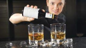 Cocktail che fa concetto Il barista fa il cocktail con l'alcool al contatore della barra, aggiungente alcune gocce al rallentator video d archivio