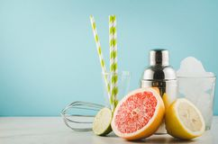 Cocktail che fa gli strumenti della barra, agitatore, frutti tropicali su un BAC blu immagine stock libera da diritti