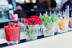 Cocktail cherries, herbs and flowers on bar Royalty Free Stock Photography