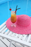Cocktail with cherry on a beach table with a straw hat near Stock Photos