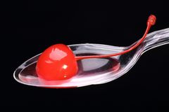 Cocktail cherry on spoon. Red cocktail cherry on transparent plastic spoon with black background Stock Image
