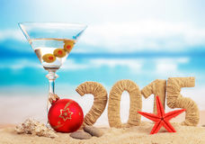 Cocktail, Christmas ball and New year sign. On sandy beach royalty free stock image