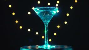 Cocktail ciano brilhante no vidro, girando no fundo escuro com luz borrada filme