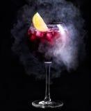cocktail Cocktail rosso scuro con ghiaccio e una fetta di limone Un cocktail nel fumo Fotografia Stock Libera da Diritti