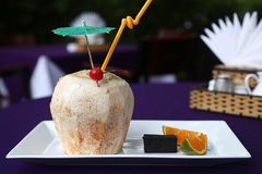 A cocktail of coconut. On the plate on her coconut cocktail Royalty Free Stock Photo