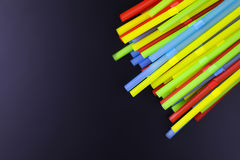 Cocktail colorful plastic tube on a black background Royalty Free Stock Images