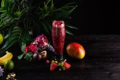 Cocktail com frutos e bagas em um vidro alto em um fundo escuro fotos de stock royalty free
