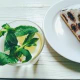 cocktail com limão e hortelã, bolo do cereja-chocolate em um fundo branco Foto de Stock