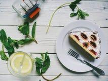 cocktail com limão, folhas de hortelã e bolo em um fundo branco Imagem de Stock Royalty Free