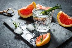 Cocktail com toranja, gelo e alecrins no fundo de pedra escuro fotografia de stock