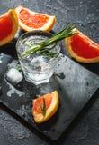 Cocktail com toranja, gelo e alecrins no fundo de pedra escuro imagem de stock royalty free