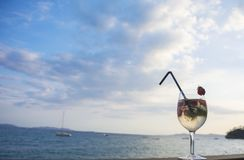Cocktail con champagne e le fragole su un fondo del mare e del cielo fotografia stock libera da diritti