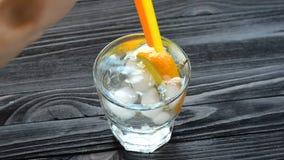 Cocktail con ghiaccio sulla tavola di legno scura archivi video