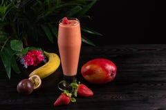 Cocktail con i frutti e bacche in un vetro alto su un fondo scuro fotografia stock libera da diritti