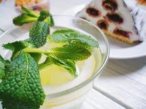 cocktail con il limone e la menta, dolce del ciliegia-cioccolato su un fondo bianco Fotografia Stock