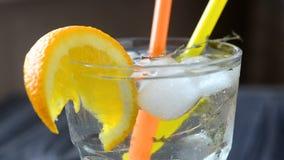 Cocktail con la fetta ed il ghiaccio arancio video d archivio