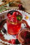 Cocktail cor-de-rosa da cor na superfície rústica decorada com bagas e Imagem de Stock Royalty Free