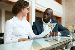 Cocktail on counter with two businesspeople in background Royalty Free Stock Photos