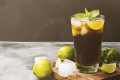 Cocktail Cuba Libre dans un verre sur un fond foncé Copiez l'espace Image stock