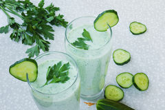 Cocktail with cucumber, fresh vegetable smoothie, parsley leaves and cucumber slices on a white table. Cocktail with cucumber, fresh vegetable smoothie, parsley Royalty Free Stock Photography