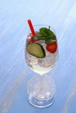 Cocktail with cucumber, strawberry in wine glass, straw Stock Photos