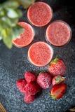 Cocktail d'alcool de fraise dans les tirs, fond noir, barre photo stock
