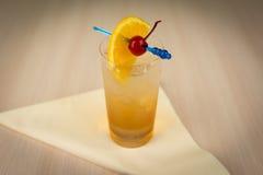 Cocktail da segale con la ciliegia e l'arancia sulla tavola di legno Immagini Stock