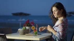 Cocktail de apreciação consideravelmente fêmea pensativo no restaurante do beira-mar, humor romântico video estoque