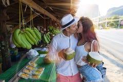 Cocktail de baiser de noix de coco de prise de jeunes couples sur le marché en plein air de la Thaïlande, les touristes homme et  Image stock