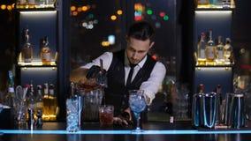 Cocktail de derramamento do empregado de bar ao vidro na barra vídeos de arquivo