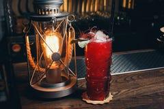Cocktail de fraise avec de la glace écrasée sur un gradient rouge Photographie stock