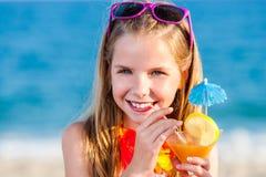 Cocktail de fruto bebendo da menina bonito na praia fotos de stock
