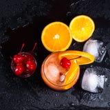 Cocktail de lever de soleil de tequila, orange, glaçon et cerises de marasquin sur un plateau noir humide d'ardoise Vue supérieur photographie stock