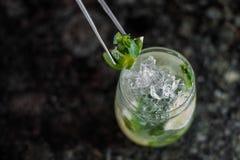 Cocktail de Mojito avec la chaux et la menthe en verre de highball sur la table en bois Fond jaune L'espace pour le texte image stock