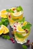 Cocktail de mojito de citron avec la menthe fraîche et la grenade, boisson régénératrice froide d'été ou boisson avec de la glace Photos libres de droits